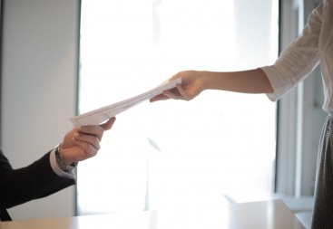 Employee giving paperwork to employer
